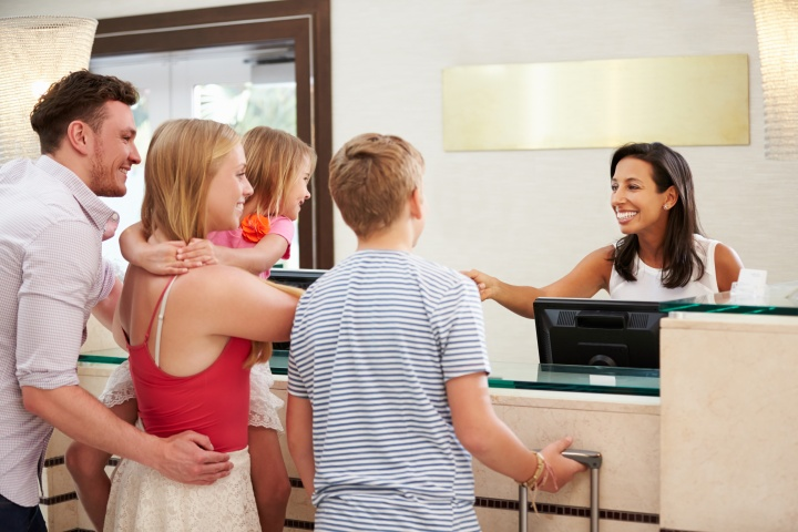 Family Checking In At Hotel Reception