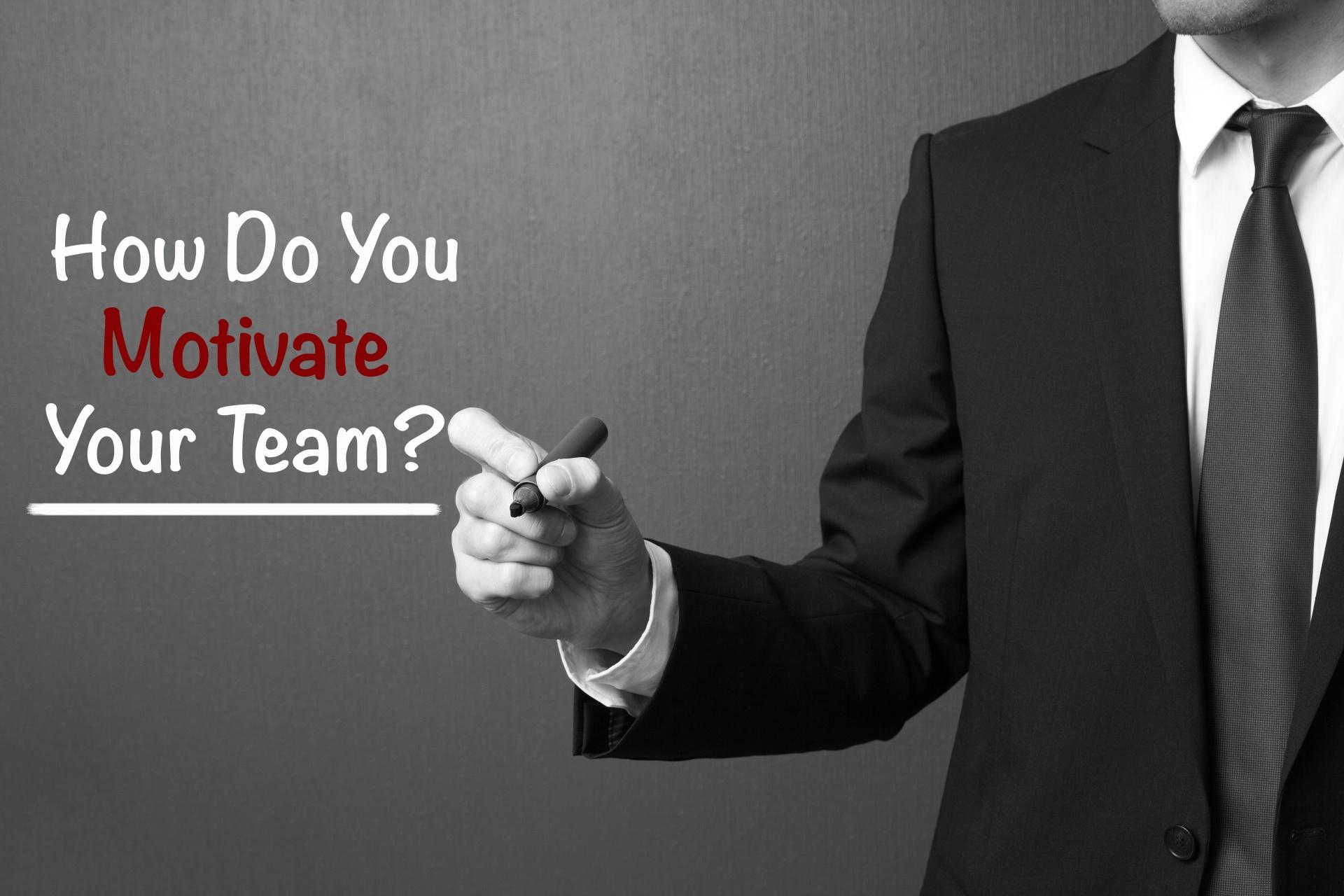 Business man writing: How Do You Motivate Your Team?