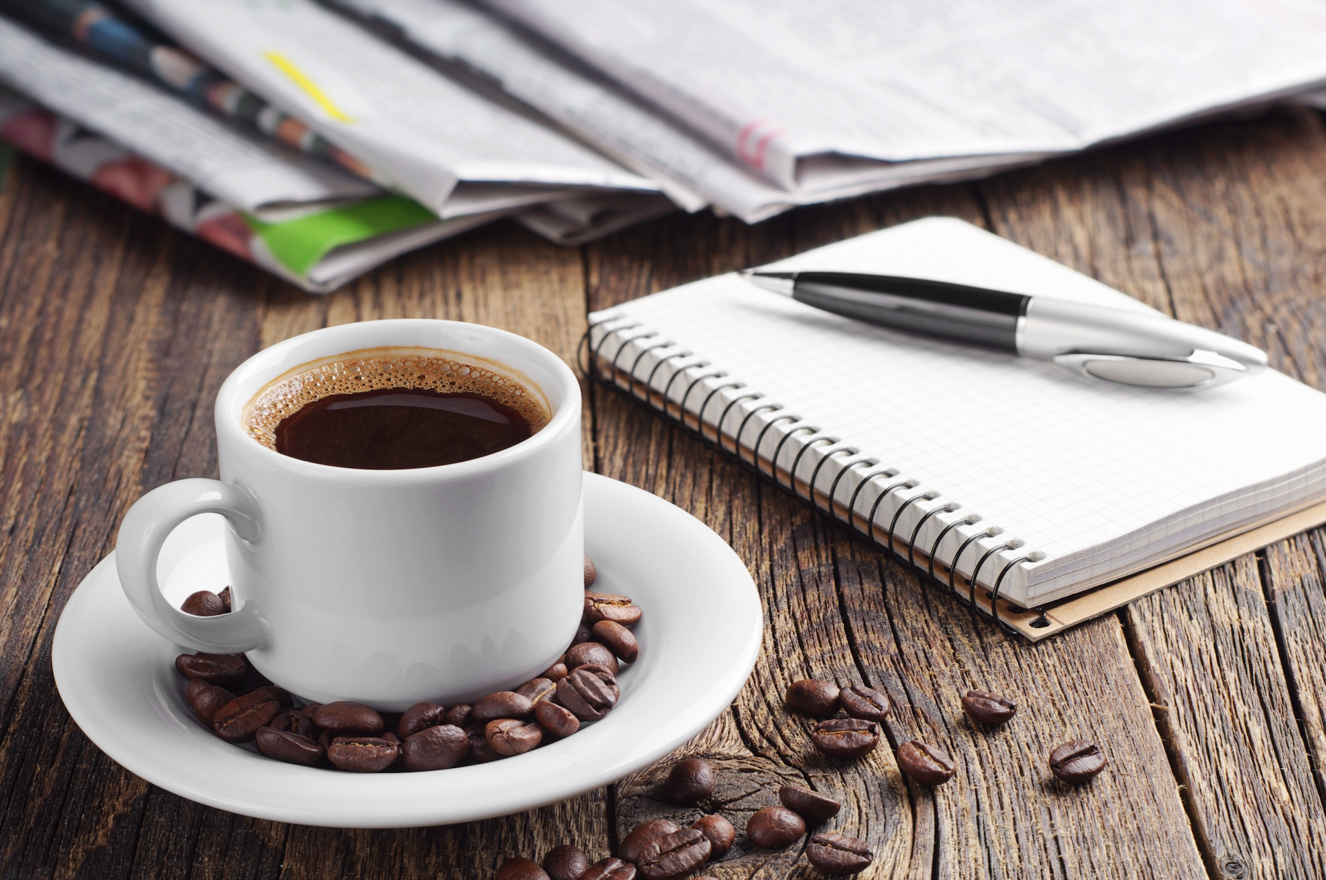 Cup of coffee, newspaper, notepad and pen on old wooden table